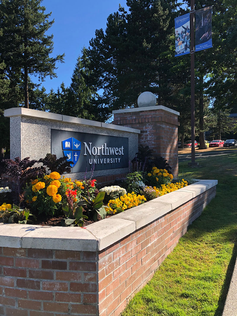 Northwest University sign, brick planter with floweres