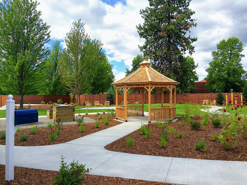 Outdoor seating, walking paths, raised planter beds, and birdhouses provide a variety of passive and active ways for residents at the Providence Adult Day Health Memory Garden to enjoy nature.