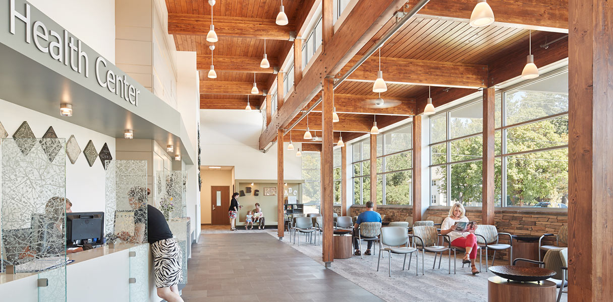 Large windows in the lobby provide a visual connection to nature, while the deliberate use of finishes and patterns serve to mimic the natural environment. Link to Newport Health Center project page