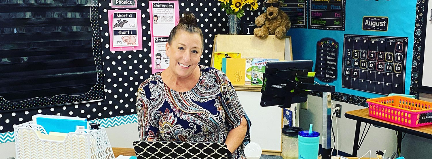 Teacher Christy Webb sitting at her desk in front of a learning wall.